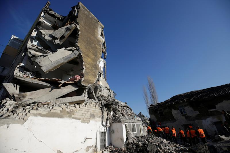 Emergency personnel work near a damaged building in Thumane, after an earthquake shook Albania, November 26, 2019. REUTERS/Florion Goga