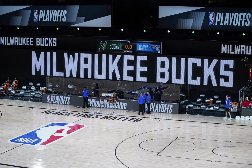 Officials stand beside an empty court at the scheduled start of an NBA game between the Milwaukee Bucks and the Orlando Magic on Aug. 26, 2020. The Milwaukee Bucks didn't take the floor in protest against racial injustice and the shooting of Jacob Blake, a Black man, by police in Kenosha, Wisconsin. (AP)