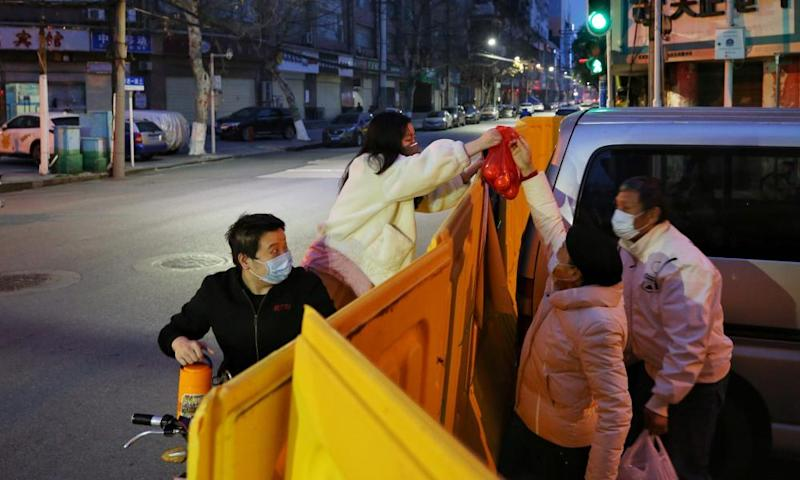 People deliver food to residents over a barrier set up to prevent people from entering or leaving a residential community in Wuhan.