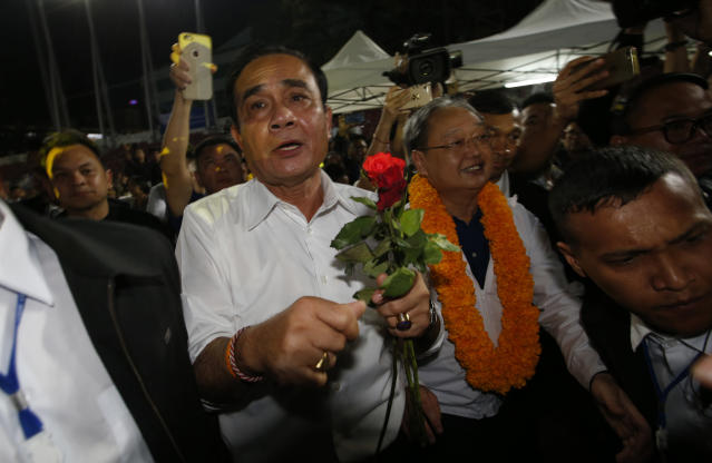 Thai Prime Minister Prayuth Chan-ocha of the Palang Pracharat Party receives flowers from supporters during an election campaign rally in Bangkok, Thailand, Friday, March 22, 2019. The political movement that has won every Thai election in nearly two decades is facing its biggest test yet: Squaring off against the allies of the military junta that removed it from power and rewrote the electoral rules with the goal of putting an end to those victories. (AP Photo/Sakchai Lalit)