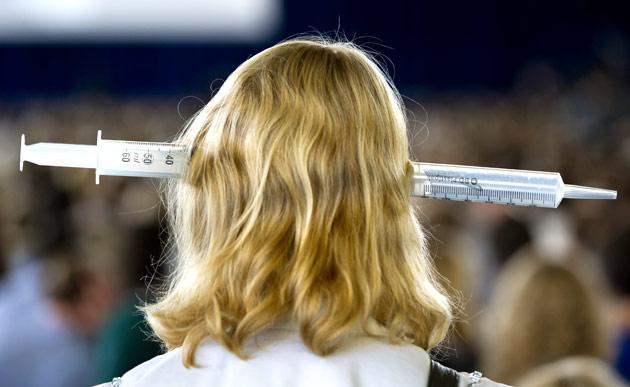 A general practitioner with a large syringe on her head takes part in a demonstration by approximately 5000 general practitioners and doctors' assistants, at the RAI in Amsterdam, on October 6, 2011. The demonstration came as a response to the government's plans to cut 132 million euros in general practitioners' care. AFP PHOTO / ANP / MARCEL ANTONISSE