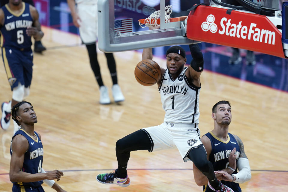 Brooklyn Nets forward Bruce Brown (1) slam dunks over New Orleans Pelicans forward Wes Iwundu (4) and center Willy Hernangomez in the first half of an NBA basketball game in New Orleans, Tuesday, April 20, 2021. (AP Photo/Gerald Herbert)
