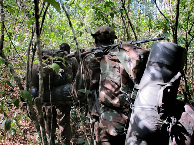 In this photo of Thursday April 19, 2012 Ugandan soldiers hunting for Joseph Kony walk through the jungle near River Vovodo, Central African Republic . For Ugandan soldiers tasked with catching Joseph Kony, the real threat is not the elusive Central Africa warlord and his brutal gang. Encounters between Ugandan troops and Lord's Resistance Army rebels are so rare that the Kony hunters worry about other things when they walk the jungle: armed poachers, wild beasts, honey bees, and even a widely-ranging fly that torments their ears during day. (AP Photo/Rodney Muhumuza)