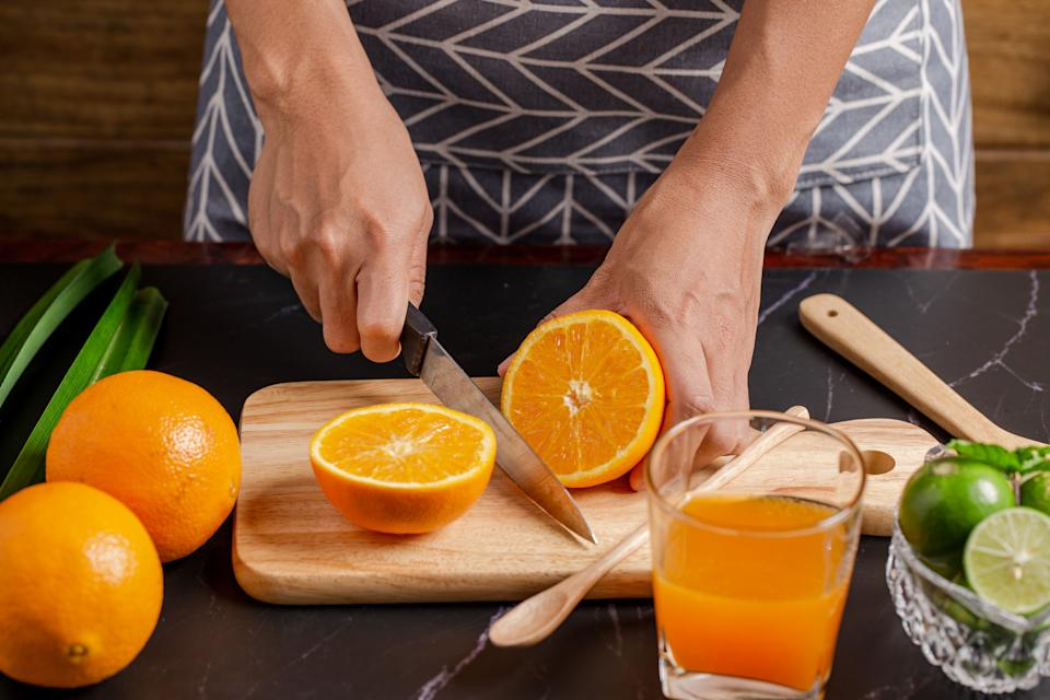 Closeup on women cutting orange for make juice on kitchen table.