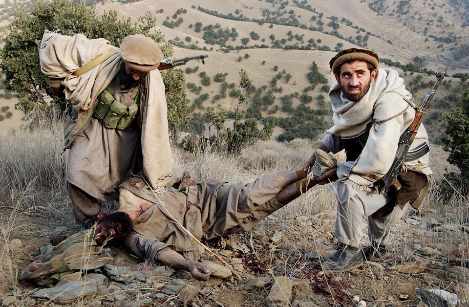 <p>Anti-Taliban soldiers carry off the body of an al Qaeda soldier they just killed in battle December 11, 2001 in the Tora Bora area of Afghanistan. Anti-Taliban forces made more gains against entrenched al Qaeda forces, prompting talks of a ceasefire and possible surrender by Osama bin Ladens terrorist organization. (Photo by Chris Hondros/Getty Images) </p>