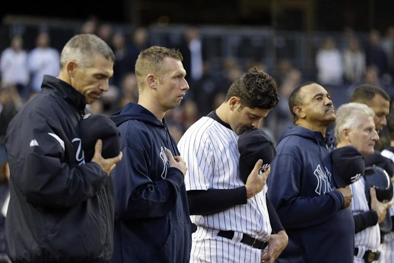 New York Yankees manager Joe Girardi, left, catcher Francisco Cervelli, third from left, and others bow their heads during a moment of silence for victims of the Boston Marathon explosions before a baseball game against the Arizona Diamondbacks at Yankee Stadium in New York, Tuesday, April 16, 2013. (AP Photo/Kathy Willens)