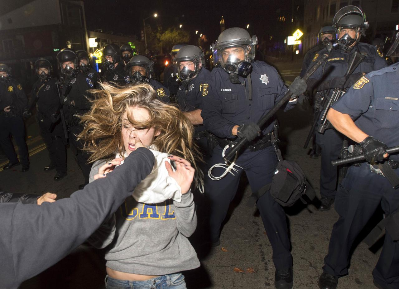 A protester flees as police officers try to disperse a crowd comprised largely of student demonstrators during a protest against police violence in the U.S., in Berkeley, California early December 7, 2014. REUTERS/Noah Berger  (UNITED STATES - Tags: CIVIL UNREST TPX IMAGES OF THE DAY)