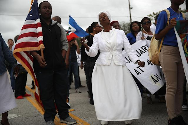 <p>Jocelyne Pierre (C) joins with others to mark the 8th anniversary of the massive earthquake in Haiti and to condemn President Donald Trump's reported statement about immigrants from Haiti, Africa and El Salvador on Jan. 12, 2018 in Miami, Fla. (Photo: Joe Raedle/Getty Images) </p>