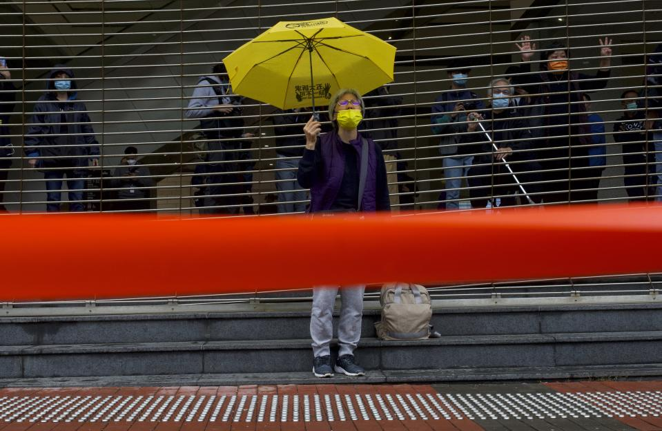 A pro-democracy supporter shouts slogans behind a police cordon line as she queues up for hearing outside a court in Hong Kong, Thursday, March 4, 2021. A marathon court hearing for 47 pro-democracy activists in Hong Kong charged with conspiracy to commit subversion enters its fourth day on Thursday, as the court deliberates over whether the defendants will be granted bail. (AP Photo/Vincent Yu)