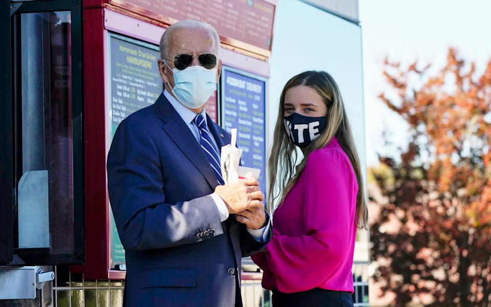 Joe Biden and his granddaughter Finnegan, stand and talk after ordering at the window at Cook Out in Durham - AP