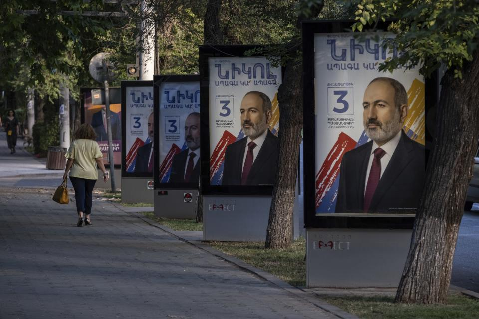 A woman walks past election posters with portraits of Armenian acting Prime Minister Nikol Pashinyan in a street in Yerevan, Armenia. June 16. 2021. Armenians head to the polls Sunday for a snap parliamentary election stemming from a political crisis that has engulfed the former Soviet nation ever since last year's fighting over the separatist region of Nagorno-Karabakh. Acting Prime Minister Nikol Pashinyan called the early vote after facing months of protests demanding his resignation following Armenia's defeat in the Nagorno-Karbakh conflict with Azerbaijan, its neighbor in the Caucasus Mountains region south of Russia. (AP Photo/Areg Balayan)