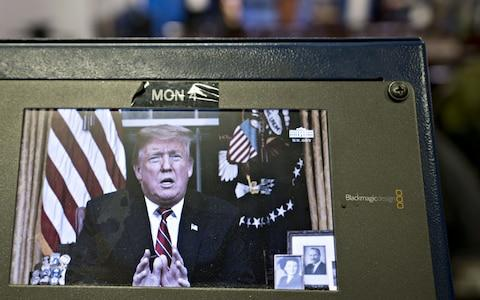 A television monitor in the White House press briefing room broadcasts U.S. President Donald Trump's address on border security  - Credit: Bloomberg