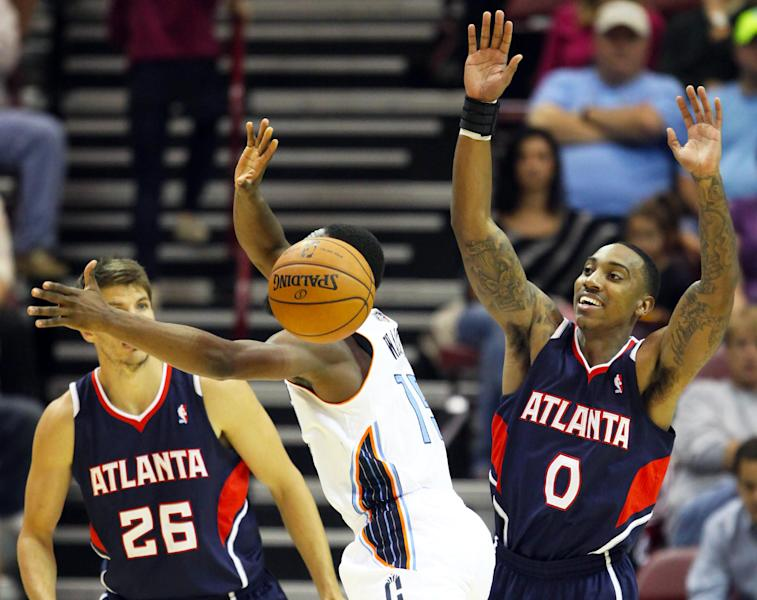 Charlotte Bobcats guard Kemba Walker, center, loses the ball with Atlanta Hawks' Kyle Korver, left, and Jeff Teague defeding during the first half of a preseason NBA basketball game in Asheville, N.C., Tuesday, Oct. 8, 2013. (AP Photo/Adam Jennings)