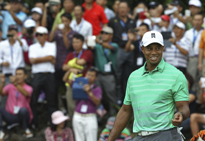 Tiger Woods of the United States smiles during an exhibition golf match against Rory Mcllory of Northern Ireland in Haikou, in southern China's island province Hainan, Monday, Oct. 28, 2013. (AP Photo/Vincent Yu)