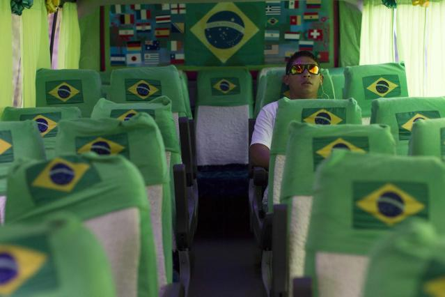 "A passenger rides a bus driven by Raimundo Queiroz and decorated for the 2014 World Cup in Manaus, May 21, 2014. Queiroz and his wife Iris Guerreiro are the owners and sole drivers of the bus that regular passengers nicknamed ""Brasileirinho padrao FIFA"" (FIFA-standard Brazilian), which they decorated to attract tourists coming to watch the World Cup. Brazil hosts the 2014 World Cup from June 12 through July 13. REUTERS/Bruno Kelly (BRAZIL - Tags: SPORT SOCCER WORLD CUP)"