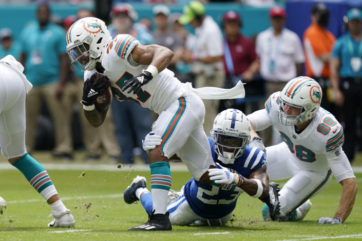 Miami Dolphins running back Myles Gaskin (37) gets tackled by Indianapolis Colts cornerback Kenny Moore II (23), as Miami Dolphins tight end Mike Gesicki (88) gives chase, during the first half of an NFL football game, Sunday, Oct. 3, 2021, in Miami Gardens, Fla. (AP Photo/Lynne Sladky)