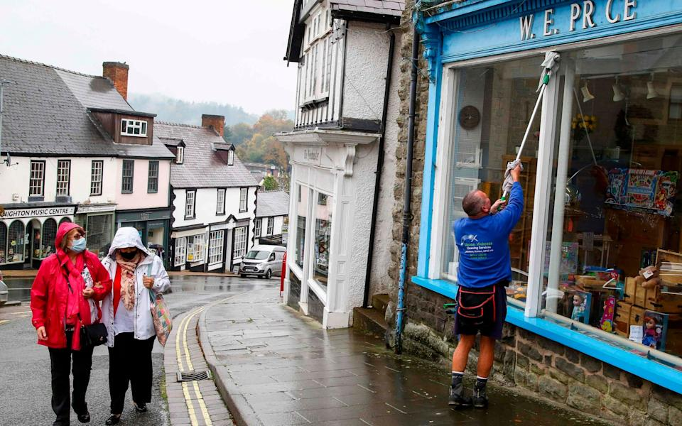 A window cleaner spruces up shops which will shut down for two weeks during Wales's firebreak - AFP
