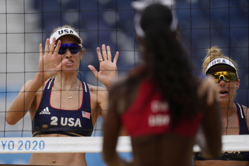 April Ross, right of the United States, and teammate Alix Klineman, left, wave to Lidianny Echevarria Benitez, center, of Cuba, After they won a women's beach volleyball match at the 2020 Summer Olympics, Monday, Aug. 2, 2021, in Tokyo, Japan. (AP Photo/Petros Giannakouris)