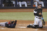 Washington Nationals' Alcides Escobar and Miami Marlins catcher Nick Fortes take their time getting up after colliding at home plate in the sixth inning of a baseball game, Tuesday, Sept. 21, 2021, in Miami. Escobar scored on the play. (AP Photo/Marta Lavandier)
