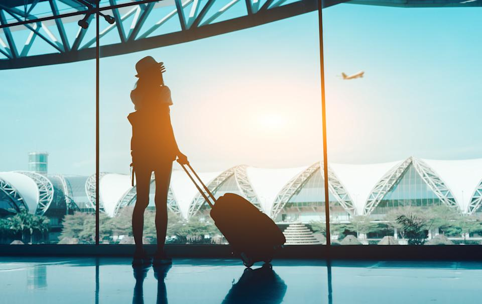 Silhouette woman travel with luggage. (PHOTO: Getty Images)