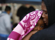 A Haitian migrant woman holds her baby as she waits in line to put her name on a migrant-run, months-long list to request U.S. asylum, alongside the El Chaparral pedestrian border crossing in Tijuana, Mexico, Friday, Nov. 30, 2018. Authorities in the Mexican city of Tijuana have begun moving some of more than 6,000 Central American migrants from an overcrowded shelter on the border to an events hall further away.(AP Photo/Rebecca Blackwell)