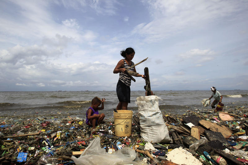 A mother and her child gather firewood and other plastic recyclable materials that were washed up along the shores of Manila Bay at the slum area in Baseco compound, metro Manila. (Photo: Romeo Ranoco/Reuters)
