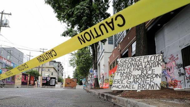 PHOTO: Caution tape is shown near a sign with the names of victims of police violence, Saturday, June 20, 2020, at the Capitol Hill Occupied Protest zone in Seattle. It is unknown who put the tape in place. (Ted S. Warren/AP)