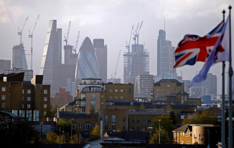A Union flag flies from a pole as construction cranes stand near skyscrapers in the City of London. Photo: Tolga Akmen/AFP/Getty Images
