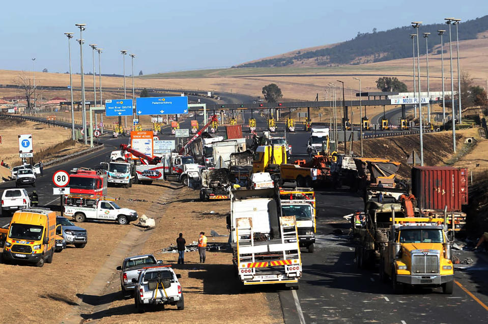 A section of a main freeway, at the Mooi River Plaza in the KwaZulu-Natal Province, South Africa, is blocked off, Saturday, July 10, 2021 after trucks were set alight in overnight protests by supporters of former South African president Jacob Zuma who was imprisoned this week for contempt of court. The protesters are demanding that Zuma be released from prison immediately. (AP Photo)