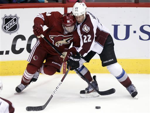 Phoenix Coyotes right winger Chris Conner, left, battles Colorado Avalanche defenseman Matt Hunwick, right, for the puck in the second period of NHL hockey game, Saturday, April 6, 2013, in Glendale, Ariz. (AP Photo/Paul Connors)