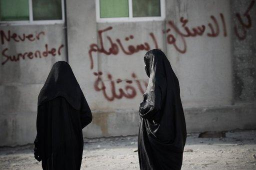 Bahraini women walk away from riot police before the start of a demonstration in Diraz, west of Manama, on May 6, 2013