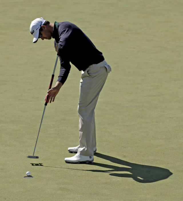 Adam Scott, of Australia, sinks a birdie putt on the first fairway during the first round of the Masters golf tournament Thursday, April 10, 2014, in Augusta, Ga. (AP Photo/Charlie Riedel)