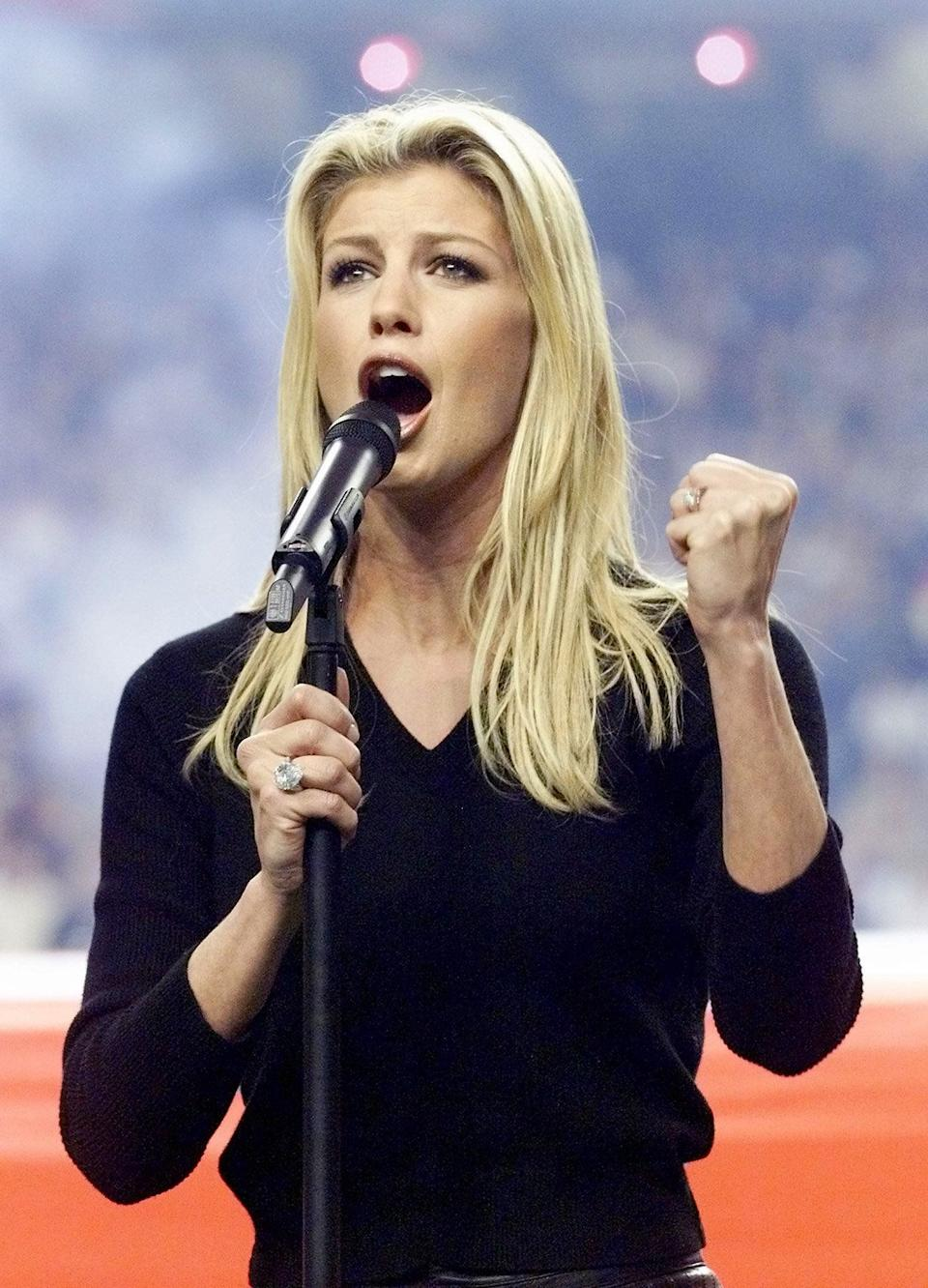US singer Faith Hill sings the US National Anthem before the start of Super Bowl XXXIV at the Georgia Dome in Atlanta Jan. 3, 2000. The St. Louis Rams and Tennessee Titans competedfor the NFL 1999 championship.
