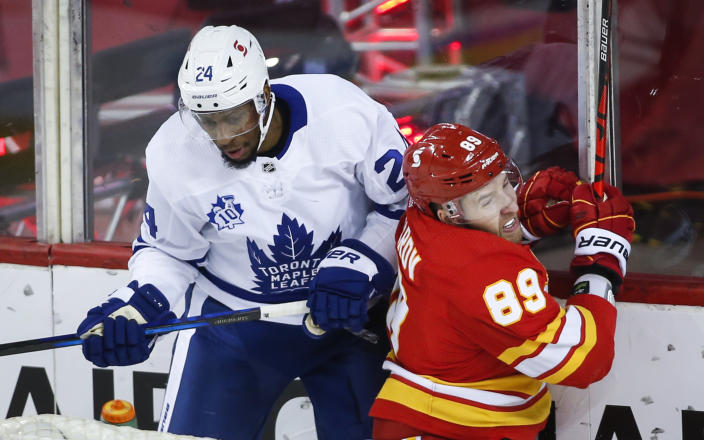 Toronto Maple Leafs' Wayne Simmonds, left, checks Calgary Flames' Nikita Nesterov during the first period of an NHL hockey game, Tuesday, Jan. 26, 2021 in Calgary, Alberta. (Jeff McIntosh/The Canadian Press via AP)