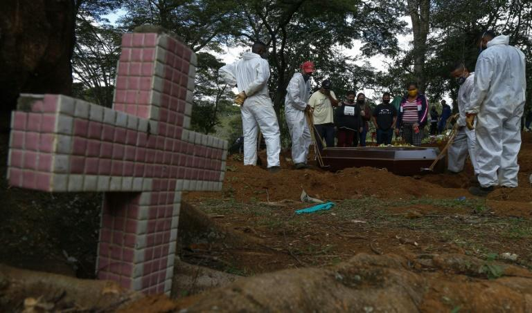 A coffin being buried at the Vila Formosa cemetery in Sao Paulo, Brazil, on April 14, 2021, as a second wave of the coronavirus pandemic forces the city to allow burials at night