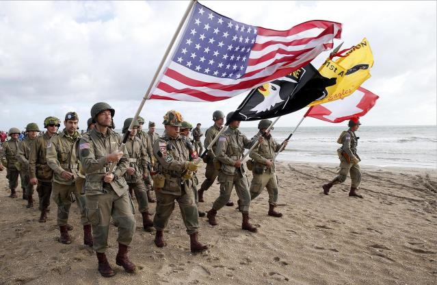 <p>Men dressed with U.S. 101st Airborne Division uniforms walk on the beach during commemorations marking the 73th anniversary of D-Day, the June 6, 1944, landings of Allied forces in Normandy. (Photo: Chesnot/Getty Images) </p>