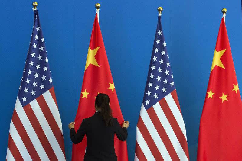 A Chinese woman adjusts a Chinese national flag next to U.S. national flags before a Strategic Dialogue expanded meeting, part of the U.S.-China Strategic and Economic Dialogue (S&ED) in Beijing