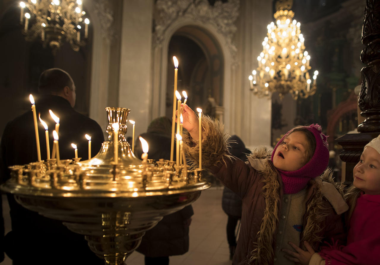 <p>A child lights a candle, during the liturgy on Orthodox Christmas Eve in the Prechistensky, the Cathedral Palace in Vilnius, Lithuania, Jan. 6, 2017. (Photo: Mindaugas Kulbis/AP) </p>