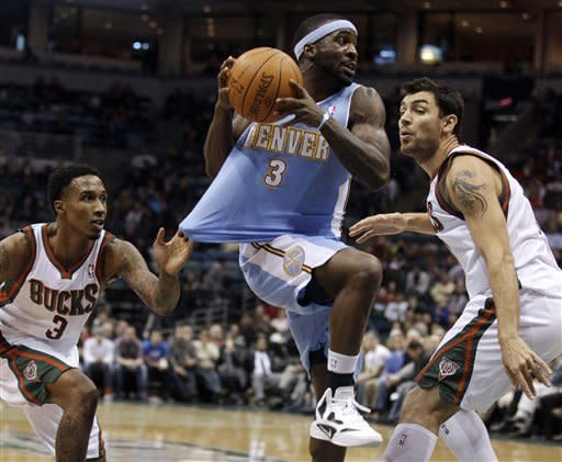 Milwaukee Bucks' Brandon Jennings grabs the jersey of Denver Nuggets' Ty Lawson as Carlos Delfino watches during the first half of an NBA basketball game Tuesday, Jan. 17, 2012, in Milwaukee. (AP Photo/Morry Gash)