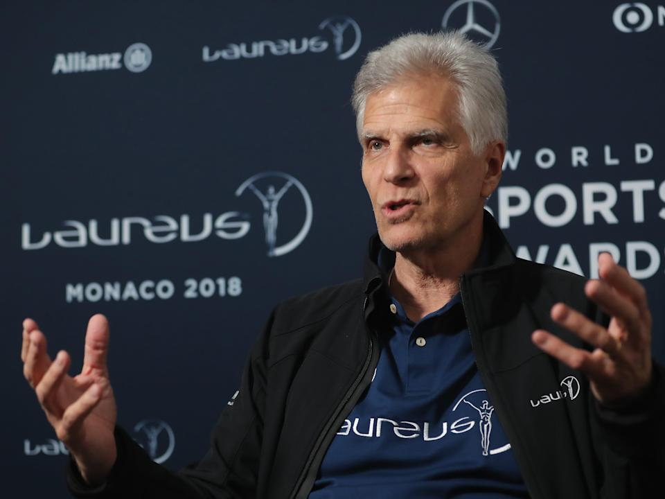 Mark Spitz using his hands to talk in front of wall