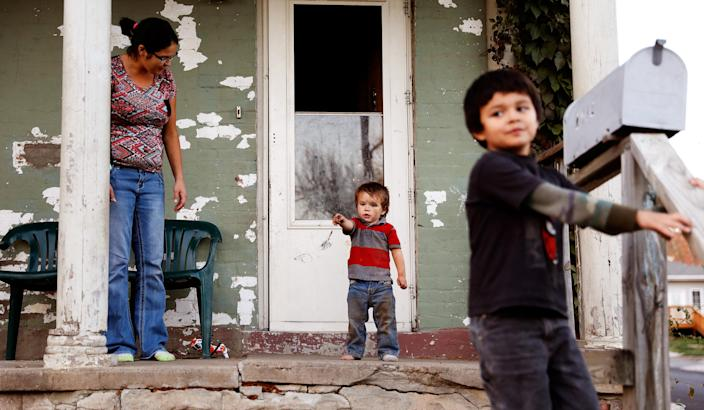Lauranda Mignery (L) watches her sons, Kadin Mignery, 2, (C) and Collin Mignery, 5, as they play on their front porch in St. Joseph, Missouri, U.S. November 15, 2016. Picture taken November 15, 2016. To match Special Report USA-LEAD/TESTING REUTERS/Whitney Curtis