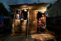 Ilma Silva Santos (R) poses with her husband Antonio Pedro de Souza (L) and two of their children outside the two-room shack in a squatter camp where they live, in Salvador, Brazil