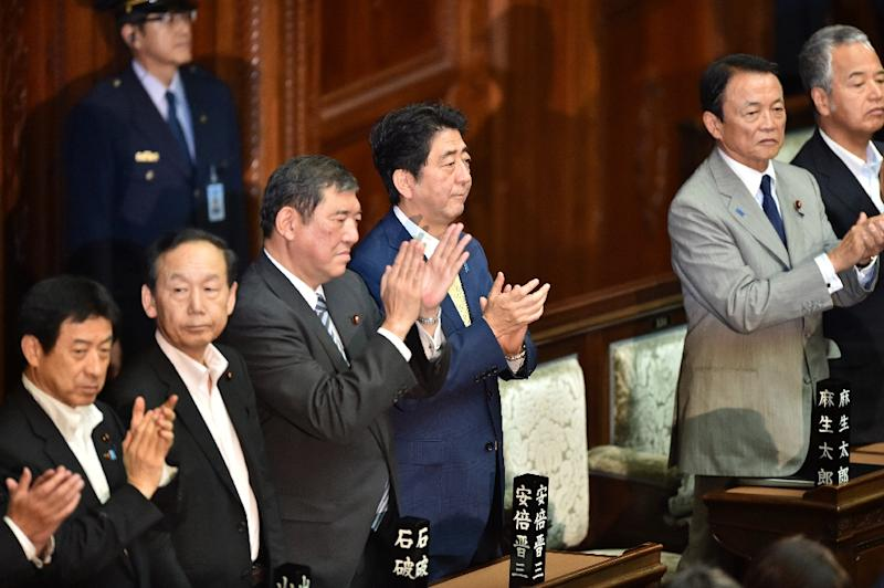 Japan's Prime Minister Shinzo Abe (3rd R) and his cabinet members applaud after controversial security bills passed the lower house in Tokyo on July 16, 2015 (AFP Photo/Kazuhiro Nogi)