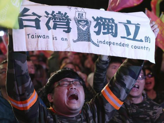 Supporters of Ms Tsai brandish a banner declaring Taiwan's independence from China (AP)