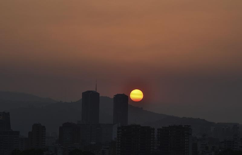 The sun sets in Caracas during a partial power cut on March 25, 2019 (AFP Photo/YURI CORTEZ)