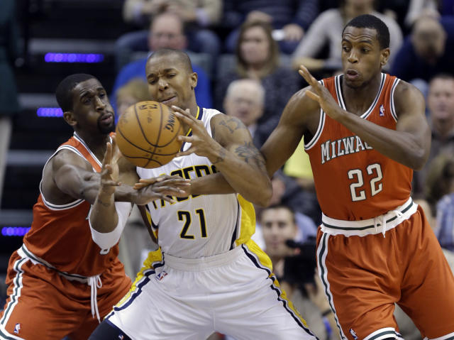 Indiana Pacers forward David West, center, is fouled after grabbing a rebound between Milwaukee Bucks forwards Ekpe Udoh, left, and Khris Middleton during the first half of an NBA basketball game in Indianapolis, Friday, Nov. 15, 2013. (AP Photo/Michael Conroy)