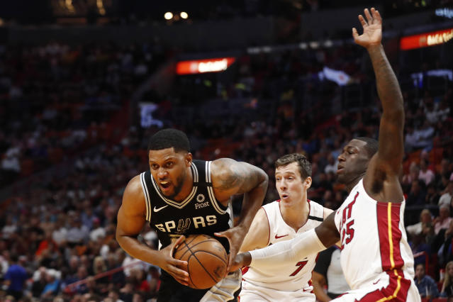 San Antonio Spurs forward Rudy Gay (22) holds the ball against Miami Heat guard Kendrick Nunn (25) and guard Goran Dragic (7) in the first half of an NBA basketball game Wednesday, Jan. 15, 2020, in Miami. (AP Photo/Brynn Anderson)