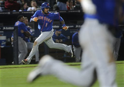 New York Mets' Jordany Valdespin (1) runs down the third base line to score on the a single by Ruben Tejada, right, during the tenth inning of a baseball game, Friday, May 3, 2013, in Atlanta. New York won 7-5. (AP Photo/John Amis)