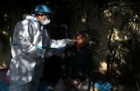 A healthcare worker collects a swab sample from a man, in New Delhi