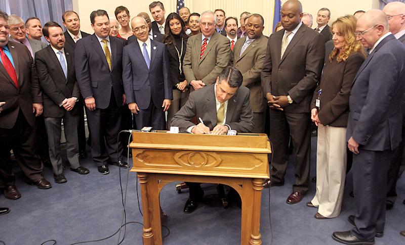Nevada Gov. Brian Sandoval signs Assembly Bill 114, the online gaming bill, on Thursday afternoon, Feb. 21, 2013 in the old assembly chambers of the Capitol in Carson City, Nev., while members of the Senate and Assembly look on. (AP Photo/Reno Gazette-Journal Out, Shannon Litz)